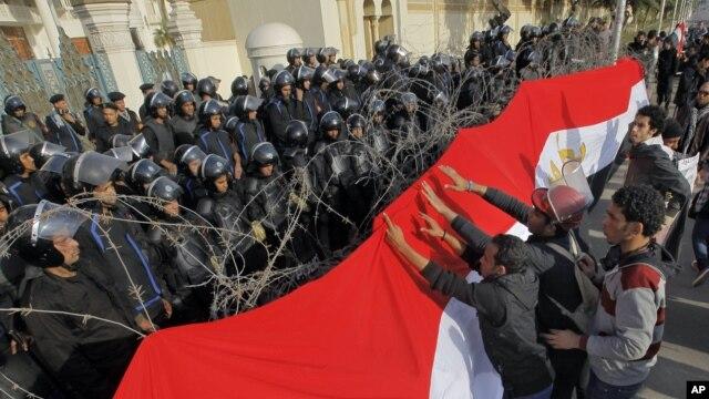 Para pengunjuk rasa Mesir memasang spanduk raksasa berwarna bendera kebangsaan Mesir di barikade kawat berduri yang dipasang di depan tentara anti huru-hara yang berjaga di depan pintu masuk istana Kepresidenan Mesir di Kairo, 25 Januari 2013. (AP Photo/Amr Nabil)
