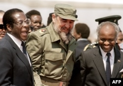 FILE - Cuban President Fidel Castro (C) is, flanked by Zimbabwean President Robert Mugabe (L), as he arrives in Harare, for the 8th non-aligned summit in Zimbabwe, Aug. 31, 1986.