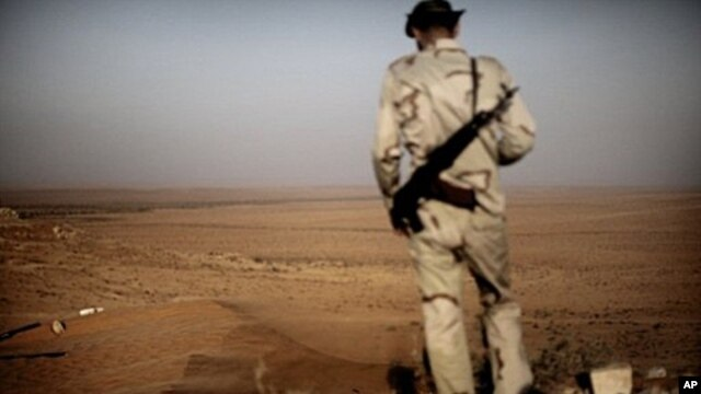 A Libyan rebel monitors Kadhafi loyalist forces as a sand storm sweeps the desert outpost of Twama, 30 km south-east of the western stronghold Zintan, on July 15, 2011. The lone outpost is the last defensive position of the rebels in the south of the Nafu