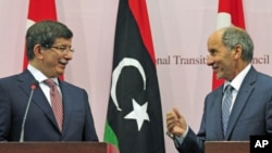 Turkish Foreign Minister Ahmet Davutoglu (L) attends a news conference with Mustafa Abdel Jalil, head of the rebel National Transitional Council, in Benghazi, August 23, 2011