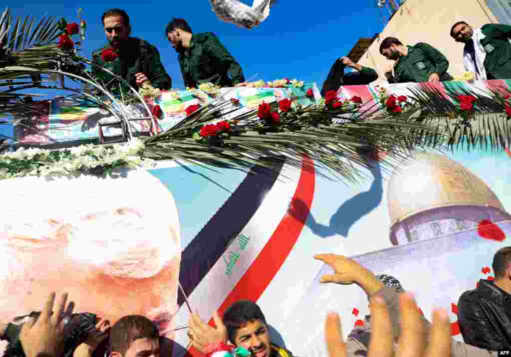 The coffins of slain top commander Qasem Soleimani and Iraqi paramilitary chief Abu Mahdi al-Muhandis, are transported atop a vehicle upon their arrival at Ahvaz International Airport in southwestern Iran. A tide of mourners packed the streets of the city of Ahvazto pay respects to top general Soleimani, days after he was killed in a U.S. strike.