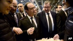 France's President Francois Hollande, center, samples some cheese as he visits the Paris international agricultural fair, Feb. 21, 2015.