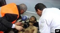 1月6号,阿拉伯联盟一位观察员(左)倾听在爆炸中受伤男子的描述