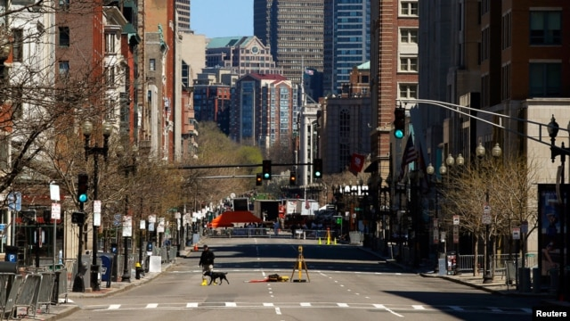 An investigator walks across Boylston Street near the site of the bombings in Boston, April 21, 2013.