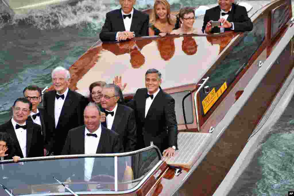 Actor George Clooney, right, waves from a boat with, from left, his father Nick Clooney, his sister Adelia Zeidler, and Ramzi Alamuddin, father of her fiancee Amal Alamuddin, on their way to the Aman hotel ahead of his wedding in Venice, Sept. 27 2014.