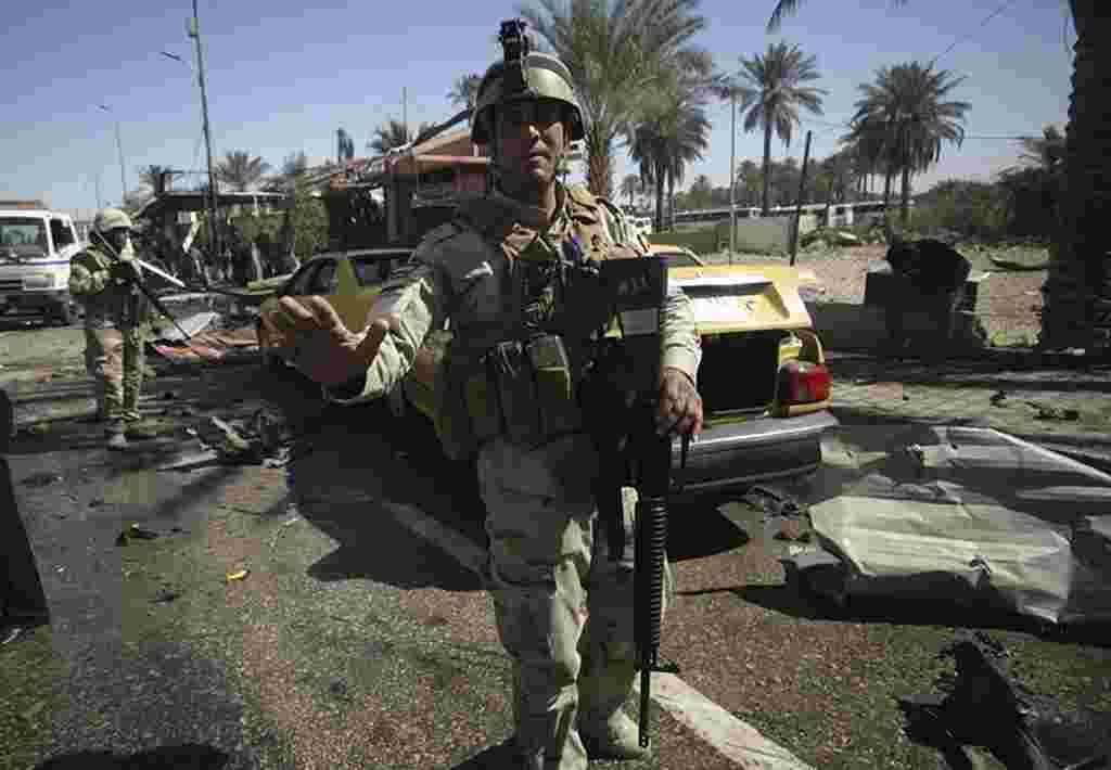 Pasukan keamanan Irak berjaga-jaga di tempat kejadian pemboman di Kerbala, sebelah selatan Baghdad (Reuters).