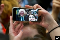 FILE - A supporter of Democratic presidential candidate Sen. Bernie Sanders, I-Vt., takes a selfie with the candidate during a campaign rally in Minneapolis, Minnesota, Feb. 29, 2016. Many states are weighing allowing selfies with voters' ballots.
