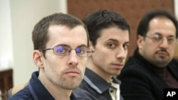 American hikers Shane Bauer (L) and Josh Fattal (C) and their translator attend the first session of their trial at the revolutionary court in Tehran, February 6, 2011