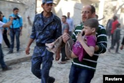 FILE - A man holds an injured boy after what activists said was a barrel bomb dropped by forces loyal to Syria's President Bashar al-Assad.