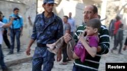 Người đàn ông ẵm bé trai bị thương vì bom thùng của lực lượng trung thành với Tổng thống Syria ném vào một trường học và tòa nhà dân cư ở khu phố Seif al-Dawla của Aleppo, ngày 3/5/2015.