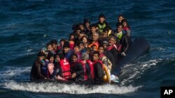 FILE - Afghan migrants on an overcrowded inflatable boat approach the Greek island of Lesbos in bad weather after crossing the Aegean Sea from Turkey, Oct. 28, 2015.