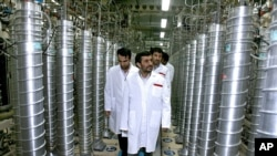 Former Iranian President Mahmoud Ahmadinejad, center, visits the Natanz Uranium Enrichment Facility some 200 miles (322 kilometers) south of the capital Tehran, Iran, April 8, 2008.