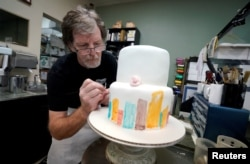 FILE - Baker, Jack Phillips, decorates a cake in his Masterpiece Cakeshop in Lakewood, Colorado, Sept. 21, 2017.