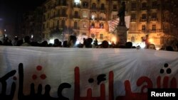 Demonstrators from various anti-military groups shout slogans during a protest against government military rules and against Egypt's Army Chief General Abdel Fattah al-Sisi, at Talaat Harab Square in downtown Cairo, Jan. 22, 2014.