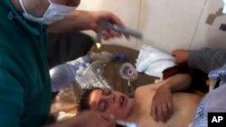 Un médico sirio tratando a un niño después de una sospecha de ataque químico.