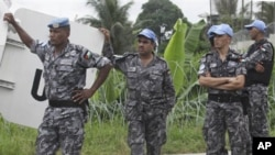 UN forces wait outside the UN headquarters during a press conference in Abidjan, Ivory Coast, Monday, Dec. 20, 2010.