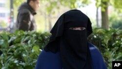 一名22岁的女性穿戴遮面面纱坐在比利时布鲁塞尔的公园(资料照片)