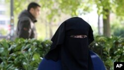 FILE - Selma, a 22 year old woman, wears the niqab as she sits in a park in Brussels.