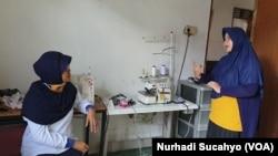 Dwi Rahayu Februarti dan Ragil Ristiyanti berbicara menggunakan bahasa isyarat, Sabtu, 18 April 2020. (Foto: Nurhadi Sucahyo/VOA)