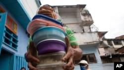 Un voluntario lleva recipientes con arroz, pollo y ensalada para los residentes del comedor de beneficencia San Antonio de Padua en el barrio Petare de Caracas, el 10 de junio de 2021.