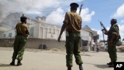 Armed police guard the Salvation Army Church after it was set on fire by rioting youths, following Friday Muslim prayers in Mombasa, Kenya, Oct. 4, 2013.