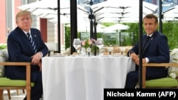 US President Donald Trump (L) sits to lunch with French President Emmanuel Macron at the Hotel du Palais in Biarritz, south-west France on August 24, 2019, on the first day of the annual G7 Summit attended by the leaders of the world's seven richest democ