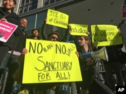 FILE - Protesters hold up signs outside a courthouse where a federal judge hears arguments in a lawsuit challenging President Donald Trump's executive order to withhold funding from communities that limit cooperation with immigration authorities, in San Francisco.