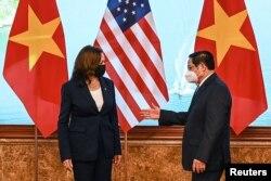 Perdana Menteri Vietnam Pham Minh Chinh (kanan) memberi isyarat kepada Wakil Presiden AS Kamala Harris di kantor Pemerintah di Hanoi, Vietnam, 25 Agustus 2021. (Manan Vatsyayana/Pool via REUTERS)