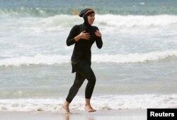 Twenty-year-old trainee volunteer surf life saver Mecca Laalaa runs in a burkini at the beach.
