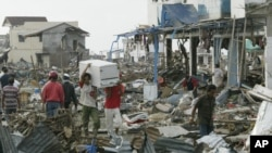 Tsunami survivors carry items they saved from a commercial area of Banda Aceh, the capital of Aceh province in northwest Indonesia. This photo was taken on December 31, 2004, five days after a tsunami destroyed the city and other coastal towns of Sumatra.
