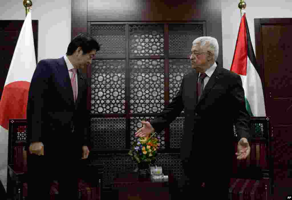 Palestinian President Mahmoud Abbas receives Japanese Prime Minister Shinzo Abe prior to their meeting at the Palestinian Authority headquarters, in the West Bank city of Ramallah, Jan. 20, 2015.