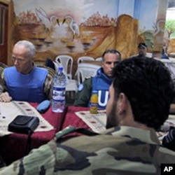 The Chief of the U.N. Supervision Mission to Syria, Norwegian Major-General Robert Mood (L) and his team meet members of the Free Syrian Army at al-Khalidiya neighborhood during a visit to Homs on May 3, 2012.