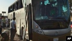 Para petugas menaikkan bus yang rusak akibat ledakan bom di Kairo, Mesir, 19 Maret 2019.