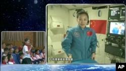 Dalam gambar yang diambil dari kamera CCTV, astronot perempuan China, Wang Yaping (nampak pada layar) sedang mendengarkan pertanyaan dari seorang pelajar putri di Beijing, China, dalam siaran langsung yang dipancarkan dari pesawat antariksa Tiangong-1 (20/6).