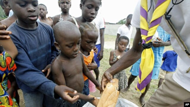A man distributes bread to children at Abidjan's St. Ambrose church, a temporary refuge for people who fled from clashes between forces loyal to Laurent Gbagbo and Alassane Ouattara (File)