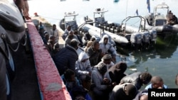 Migrants sit in a port, after being rescued at sea by Libyan coast guard, in Tripoli, Libya, April 11, 2016.