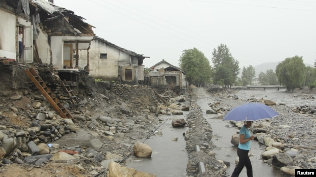 A woman holding an umbrella walks past near damaged houses by recent flooding in Kujang district, in the province of North Pyongan, August 28, 2012.