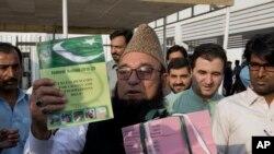 قومی اسمبلی کے اجلاس کے بعد ایک رکن اسمبلی بجٹ کی کاپی دکھا رہے ہیں