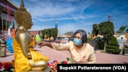 A woman pours water on the Buddha statues during traditional Thai New Year celebrations or the Songkran festival at Wat Thai Los Angeles Temple, Los Angeles, CA, April 11, 2021.
