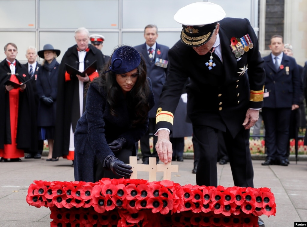 Britain's Meghan, Duchess of Sussex, places a cross during the 91st Field of Remembrance at Westminster Abbey in London.