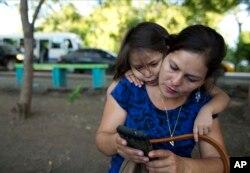 Araceli Ramos, con su hija de cinco años, Alexa, mirando por encima del hombro, mira las fotos en Facebook publicadas por la familia adoptiva de Alexa en Michigan, durante una entrevista en un parque en San Miguel, El Salvador, el 18 de agosto. 2018.