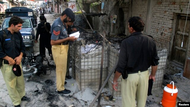Policemen collect evidence outside a prison following a Taliban attack in Dera Ismail Khan, Pakistan, July 30, 2013.