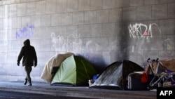 Un homme passe devant des tentes dans un campement improvisé des sans-abris dans le quartier de Tiergarten à Berlin, Allemagne, 1er mars 2018.