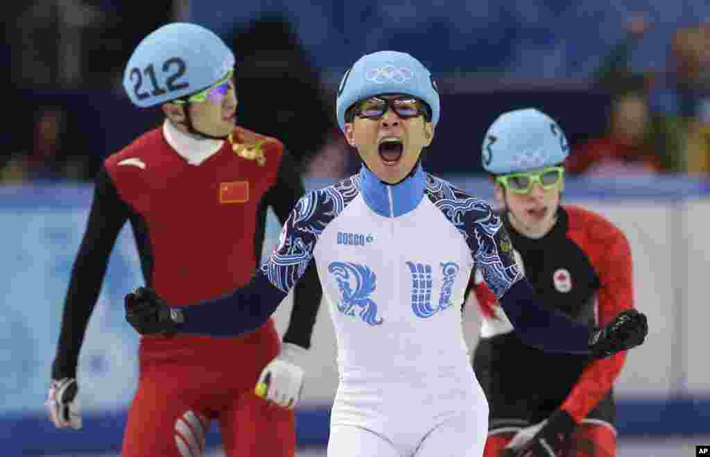 Victor An of Russia reacts as he crosses the finish line ahead of Wu Dajing of China and Charle Cournoyer of Canada in the men's 500m short track speedskating final at the Iceberg Skating Palace, Feb. 21, 2014.