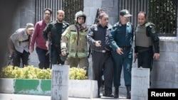 Para anggota pasukan keamanan Iran pada saat terjadinya serangan terhadap parlemen Iran di Teheran hari Rabu (7/6).