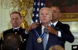 FILE - President Barack Obama presents Vice President Joe Biden with the Presidential Medal of Freedom during a ceremony in the State Dining Room of the White House in Washington, Jan. 12, 2017.
