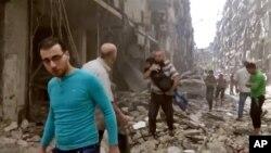 Warga di antara puing-puing bangunan yang rusak karena serangan udara di Aleppo (28/4).