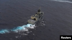 지난해 4월 호주 해군함이 뉴질랜드 공군기의 지원을 받아 말레이시아 실종 여객기 수색 작업을 벌이고 있다. (자료사진)