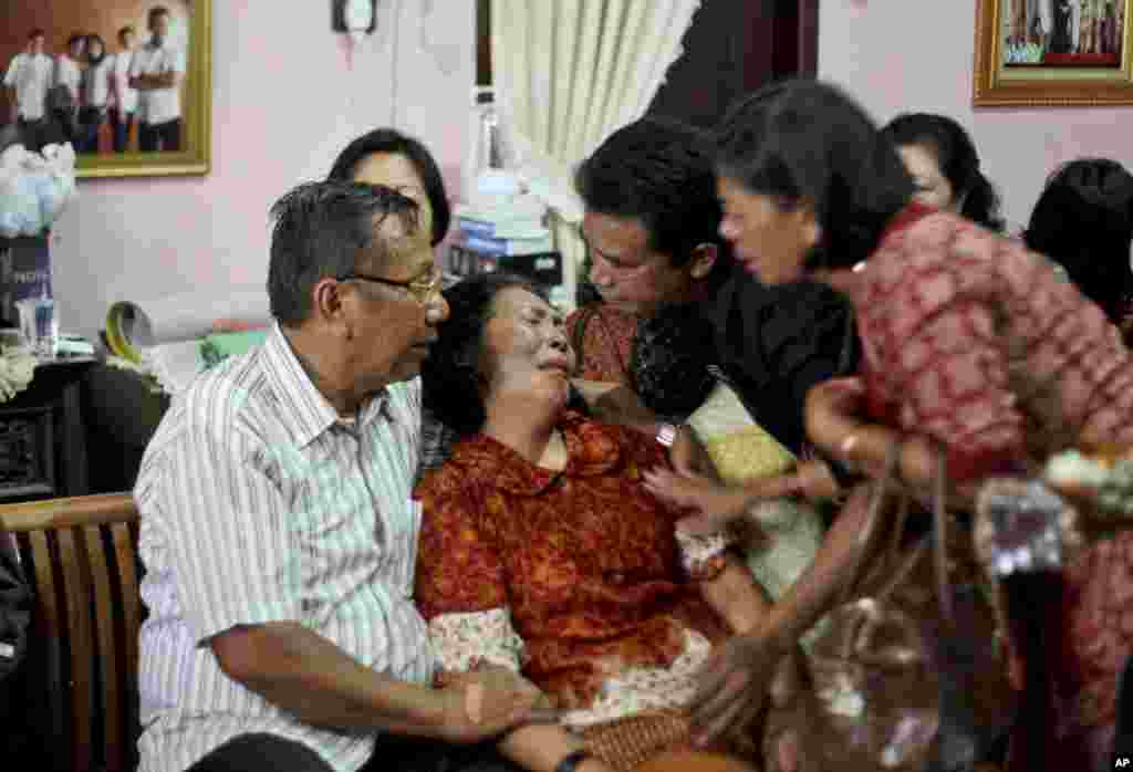 Family members comfort Chrisman Siregar, left, and his wife Herlina Panjaitan, the parents of Firman Siregar, one of the Indonesian citizens registered on the manifest of the Malaysia Airlines jetliner flight MH370 that went missing, Medan, North Sumatra, Indonesia, March 9, 2014.