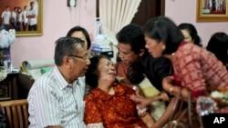 Para anggota keluarga menenangkan Chrisman Siregar (kiri) dan istrinya Herlina Panjaitan, orangtua Firman Siregar, penumpang pesawat Malaysia Airlines yang hilang asal Indonesia. (AP/Binsar Bakkara)